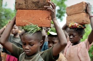 Girls carry bricks in the town of Zemio in Uganda