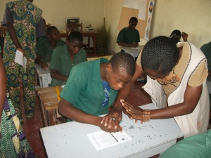 Teacher helps pupil fill out ballot